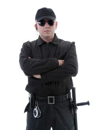 Policeman or security guard wearing black uniform and glasses standing confidently with folded arms, shot on white