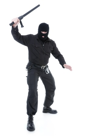 Anti-terrorist police guy wearing black uniform and black mask holding firmly police club in one hand raised in the air ready for action, shot on white photo