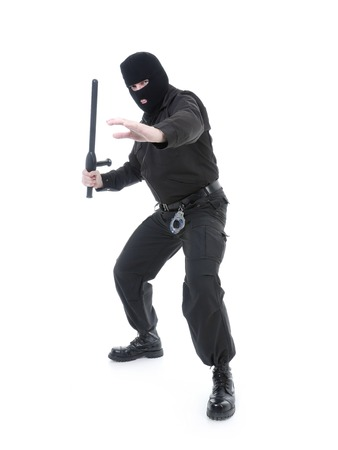 Anti-terrorist police guy wearing black uniform and black mask holding firmly police club in one hand ready for action, shot on white photo