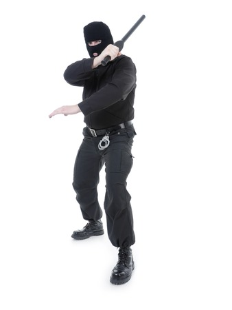 anti terrorist: Anti-terrorist police guy wearing black uniform and black mask holding firmly police club in one hand raised in the air ready for action, shot on white