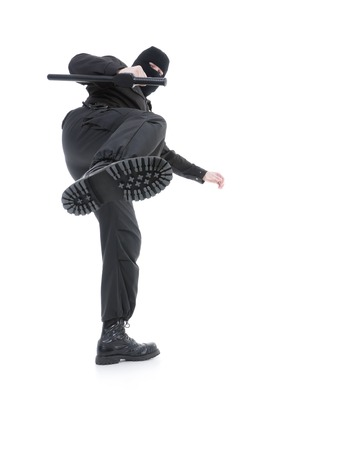anti terrorist: Anti-terrorist police guy wearing black uniform and black mask making a side kick, shot on white