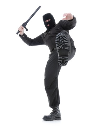 Anti-terrorist police guy wearing black uniform and black mask making a kick, shot on white photo