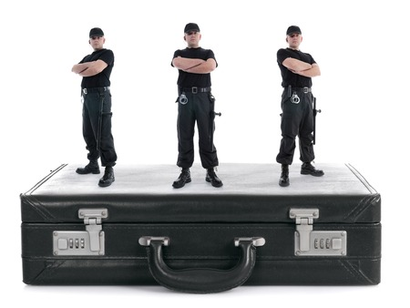 guarding: Three security guys standing on black cipher suitcase shot on white, security concept