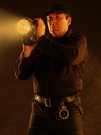 Policeman with lit torch searching the area
