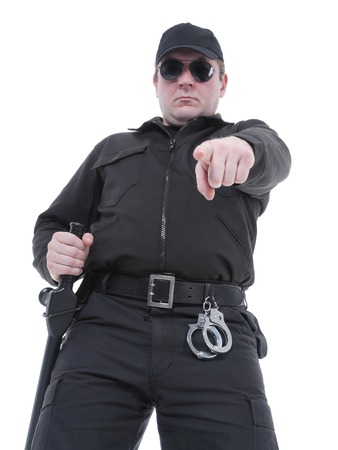 Policeman wearing black uniform and glasses pointing in ordering manner photo