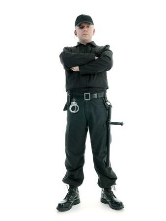 Beveiliging man met zwarte uniform uitgerust met politie club en handboeien die zich vol vertrouwen met de armen gekruist, geschoten op wit