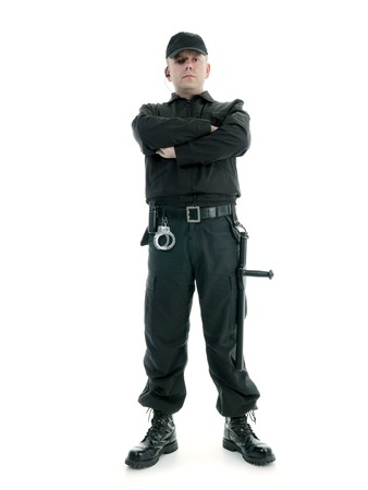 Security man wearing black uniform equipped with police club and handcuffs standing confidently with arms crossed, shot on white Imagens