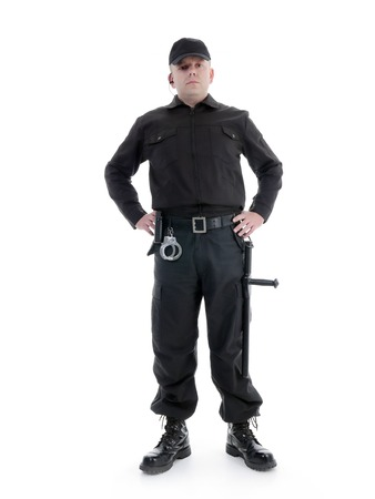 Security man wearing black uniform equipped with police club and handcuffs standing confidently with hands resting on hip , shot on white