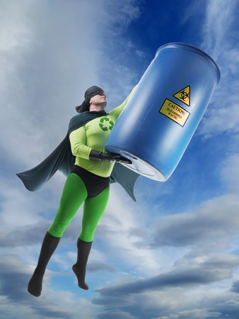 Eco superhero taking away blue container containing hazardous waste high from Earth photo