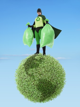 clean environment: Eco superhero holding two plastic bags full of garbage standing on green Earth planet - clean environment concept Stock Photo