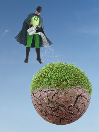 Eco superhero watering half-green half-dry planet from above - green environment concept photo