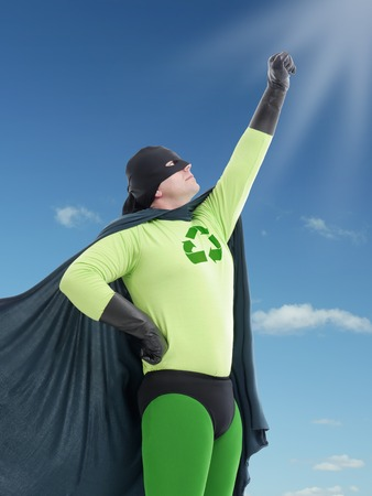 Eco superhero looking towards the Sun with his hand raised up and pointing the same direction photo