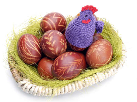 brooder: Crochet sitter sitting on easter eggs in wicker basket shot on white