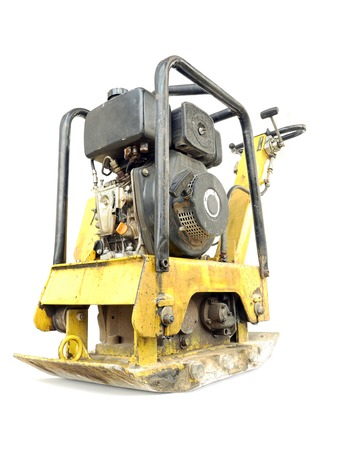 compacting: Old yellow plate compactor isolated on white