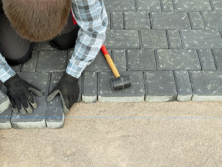 paving stone: Paver laying driveway pavement out of concrete pavement blocks Stock Photo