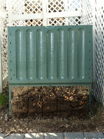 decomposition: Green plastic compost bin with lower part removed to show advanced soil decomposition process Stock Photo