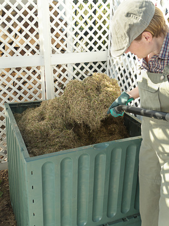 Female gardener turning over compost bin content using pitchfork to speed up decomposting process photo