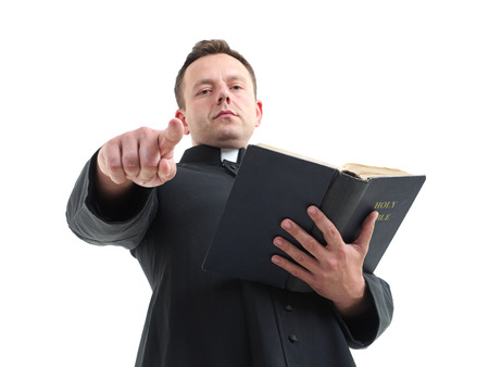 Catholic priest preaching holding open the Bible book shot on white photo