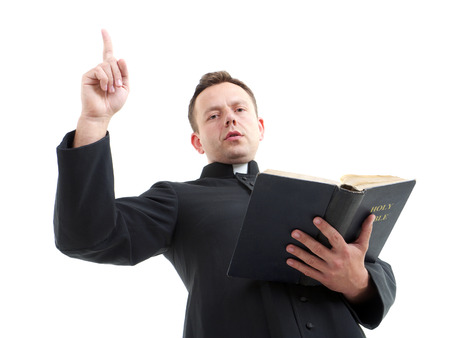 preaching: Catholic priest preaching holding open the Bible book shot on white Stock Photo