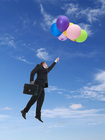 flying man: Businessman wearing black suit holding suitcase flying in the air being raised by bunch of colorful balloons Stock Photo