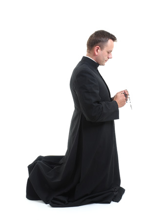 sotana: Sacerdote católico klneeling y diciendo el rosario