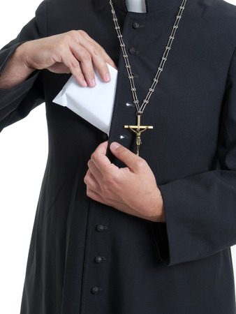 cupidity: Catholic priest putting thick envelope staffed with bribe money into cassock