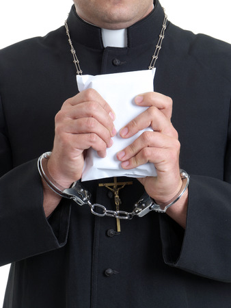 cupidity: Catholic priest handcuffed holding envelope staffed with bribe money