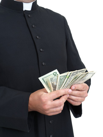 cupidity: Catholic priest with bunch of dollar banknotes Stock Photo