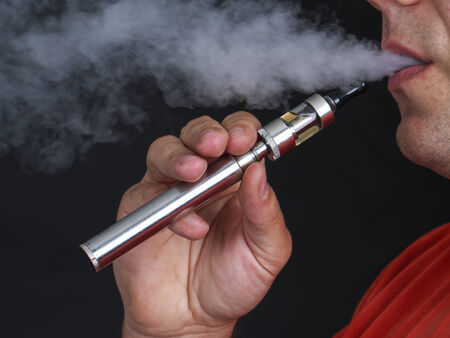 Closeup of man using e-cigarette and exhaling vapor shot over black background photo