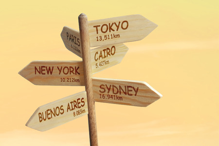 distances: Wooden signpost indicating six world capitals with distances in kilometers