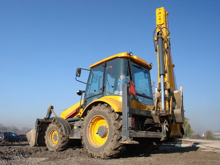 Yellow backhoe loader parked against clear blue sky photo