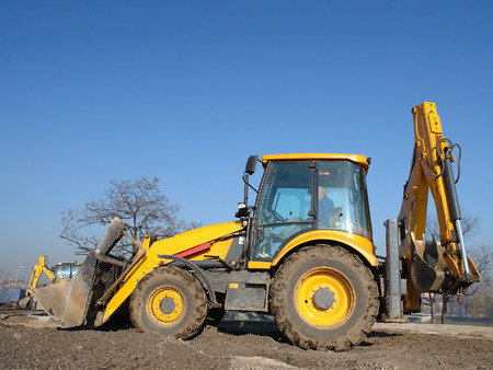heavy equipment operator: Yellow backhoe loader parked against clear blue sky