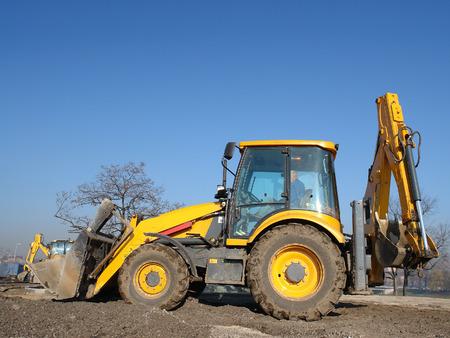 backhoe loader: Yellow backhoe loader parked against clear blue sky