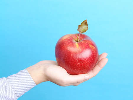 big apple: Closeup of female hand offering a giant red apple over blue background