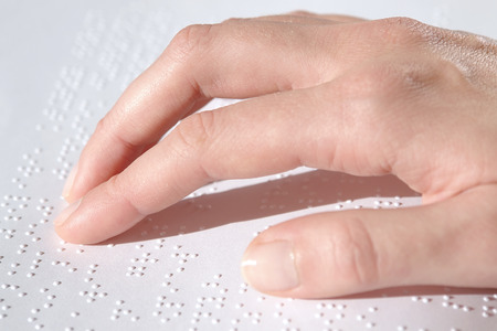 Blind reading text in braille language photo