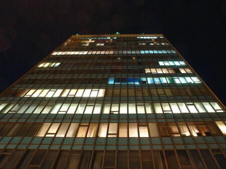 nightime: Primo piano di edificio per uffici di facciata in notturna con le luci interne su