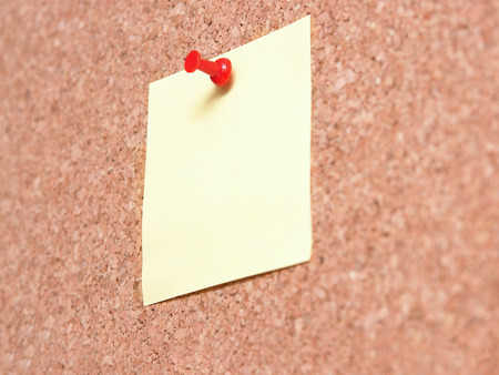 affixed: Yellow blank post-it note affixed to the corkboard with red pin Stock Photo