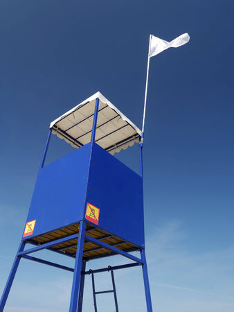 lifeguard tower: Blue lifeguard tower with white flag over clear blue sky