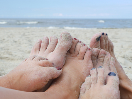 feet in sand: Group of male and female playful feet on the beach with the sea in the background