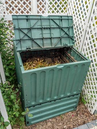 Green plastic compost bin full of organic and domestic food scraps Banque d'images