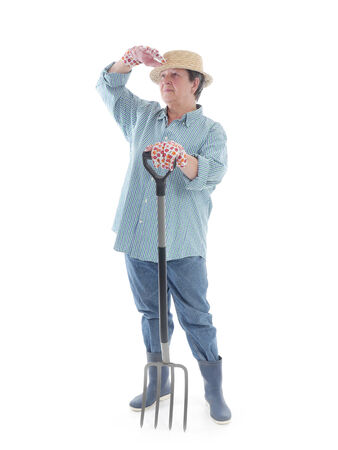 looking ahead: Senior woman gardener wearing straw hat and rubber boots resting on forks and looking ahead shot over white background