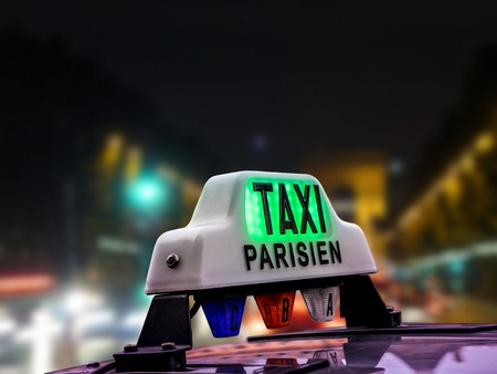elysees: Closeup of Parisian taxi cab against the blurred Champs Elysees at night, Paris, France Stock Photo