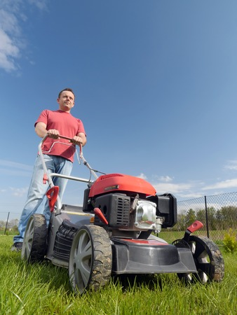 mowing grass: Man mowing grass with grass-mower  Stock Photo