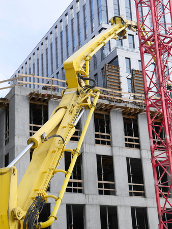 pumping: Highrise buildings under construction and yellow ready mix concrete pump to supply concrete mix up above Stock Photo