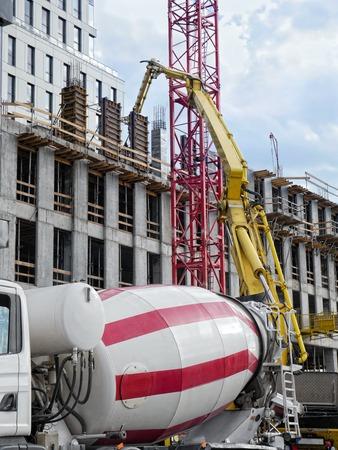 concrete pump: Highrise building under construction and ready mix concrete pump delivering concrete up above