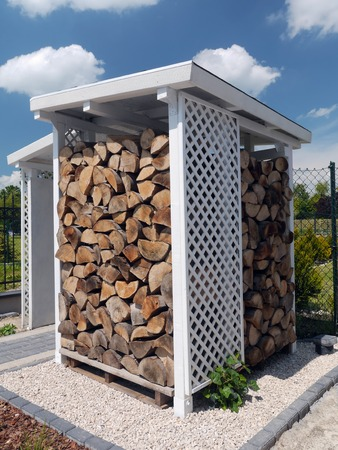 woodshed: White wooden woodshed with neatly arranged chopped firewood