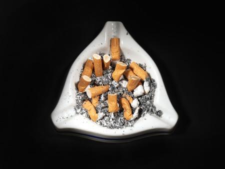 tabaco: Blanco cenicero de cerámica lleno de colillas de cigarrillos en el fondo negro Foto de archivo