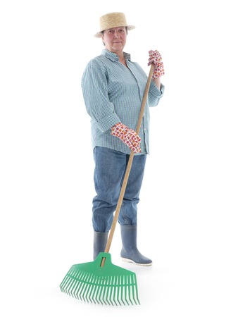 rake: Senior woman gardener wearing straw hat and rubber boots posing with plastic lawn rake over white