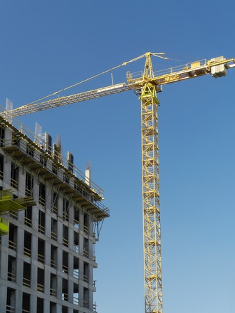 jib: Highrise building under construction and jib crane over clear blue sky