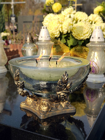 votive candle: Glass votive candle lit on black marble tombstone